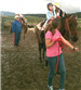An Adult Guiding a Horse While a Child is Horseback Riding